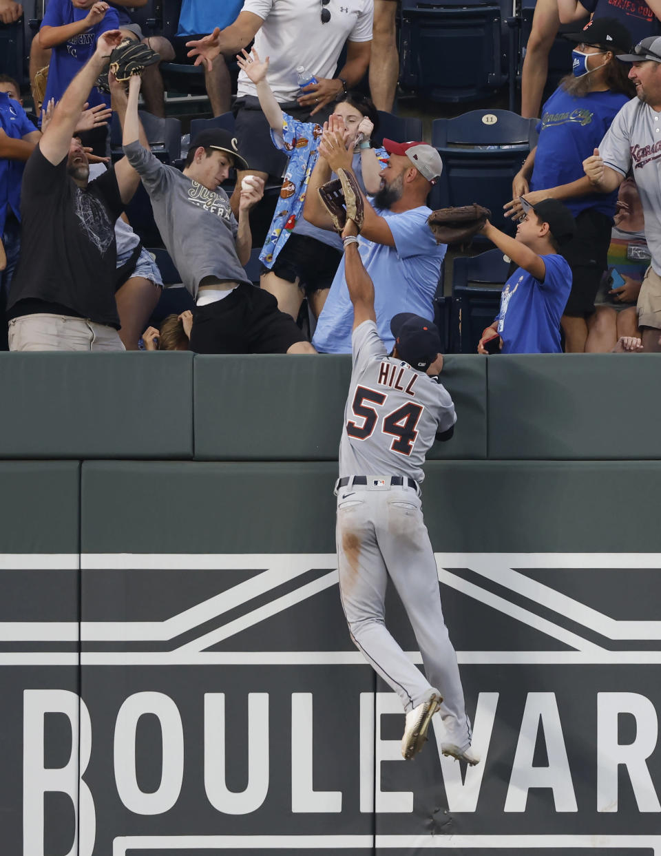 Detroit Tigers center fielder Derek Hill (54) goes up the wall in an attempt to grab a three-run home run hit by Kansas City Royals' Ryan O'Hearn during the fourth inning of a baseball game at Kauffman Stadium in Kansas City, Mo., Friday, July 23, 2021. (AP Photo/Colin E. Braley)