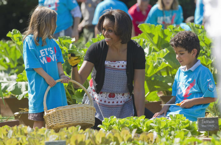 """FILE - In this June 3, 2011, file photo, first lady Michelle Obama tends the White House garden in Washington, with a group of children as part of the """"Let's Move!"""" campaign. Michelle Obama has a new look, both in person and online, and with the president's re-election, she has four more years as first lady, too. The first lady is trying to figure out what comes next for this self-described """"mom in chief"""" who also is a champion of healthier eating, an advocate for military families, a fitness buff and the best-selling author of a book about her White House garden. For certain, she'll press ahead with her well-publicized efforts to reduce childhood obesity and rally the country around its service members. (AP Photo/Evan Vucci, File)"""