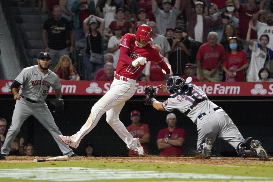 Los Angeles Angels designated hitter Shohei Ohtani, center, avoids a tag by Houston Astros catcher Jason Castro, right, but misses the plate as relief pitcher Yimi Garcia watches during the 10th inning of a baseball game Wednesday, Sept. 22, 2021, in Anaheim, Calif. Ohtani was later tagged out by Castro. (AP Photo/Mark J. Terrill)