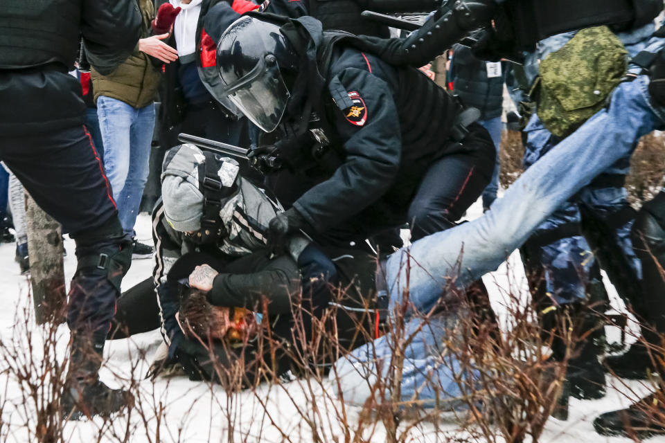Riot police detain a demonstrator with a bloody face during a protest against the jailing of opposition leader Alexei Navalny in Pushkin square in Moscow, Russia, Saturday, Jan. 23, 2021. Russian police arrested more than 3,400 people Saturday in nationwide protests demanding the release of opposition leader Alexei Navalny, the Kremlin's most prominent foe, according to a group that counts political detentions. In Moscow, an estimated 15,000 demonstrators gathered in and around Pushkin Square in the city center, where clashes with police broke out and demonstrators were roughly dragged off by helmeted riot officers to police buses and detention trucks. Some were beaten with batons. (AP Photo/Alexander Zemlianichenko)