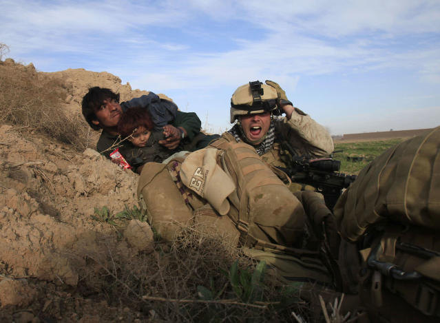 <p>U.S. Marine Lance Corporal Chris Sanderson, 24, from Flemington, New Jersey shouts as he tries to protect an Afghan man and his child after Taliban fighters opened fire in the town of Marjah, in Nad Ali district, Helmand province, Feb. 13, 2010. (Photo: Goran Tomasevic/Reuters) </p>