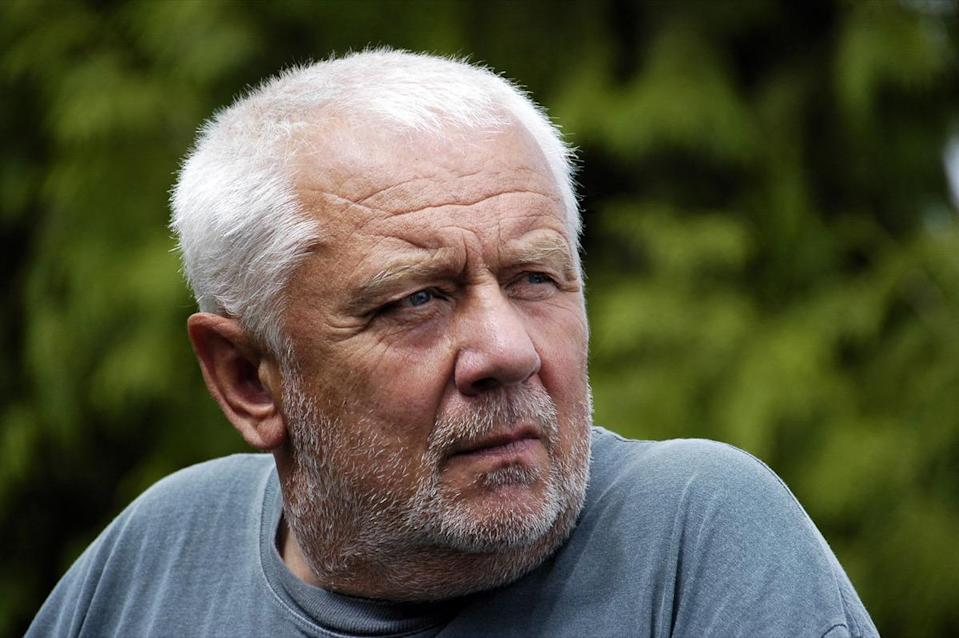 Unshaved older man with short white hair.
