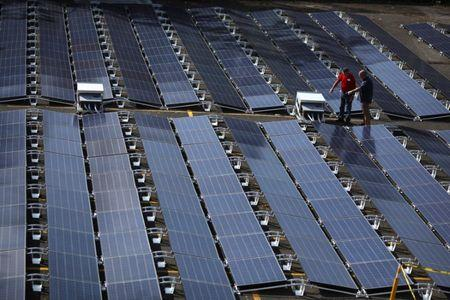 FILE PHOTO: Men gesture next to solar panels set up by Tesla, at the  San Juan Children's Hospital, after the island was hit by Hurricane Maria in September, in San Juan, Puerto Rico October 26, 2017. REUTERS/Alvin Baez/File Photo