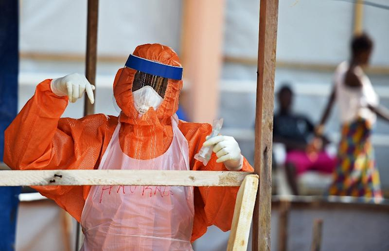 A health worker wearing personal protective equipment works on November 11, 2014 in the red zone of the Hastings treatment center outside Freetown