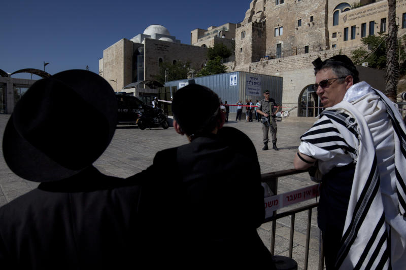 "A border police officer stands guard as ultra-Orthodox Jewish men look at the scene of a shooting at the plaza of the Western Wall, the holiest site where Jews can pray, in Jerusalem's old city, Friday, June 21, 2013. Israeli police say a guard has shot a Jewish man dead at the key Jerusalem holy site. Police spokesman Micky Rosenfeld says a private security guard at the Western Wall ""fired a number of shots"" at a man who appeared suspicious. The guard told police the man, an Israeli, had his hands in his pockets and shouted in Arabic just before the guard opened fire, Rosenfeld said. The man, in his 40s, died at the scene. (AP Photo/Sebastian Scheiner)"