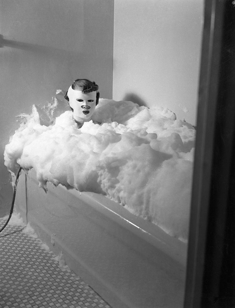<p>A woman wears a contouring compression mask as she sits in a tub in 1937. The bath is pumped with milk powder to make the water bubble. </p>