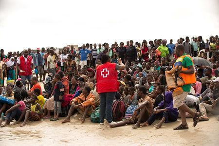 Survivors of Cyclone Idai, listen to a volunteer from Mozambique Red Cross, after arriving to an evacuation centre in Beira, Mozambique, March 21, 2019. Denis Onyodi/Red Cross Red Crescent Climate Centre/Handout via REUTERS