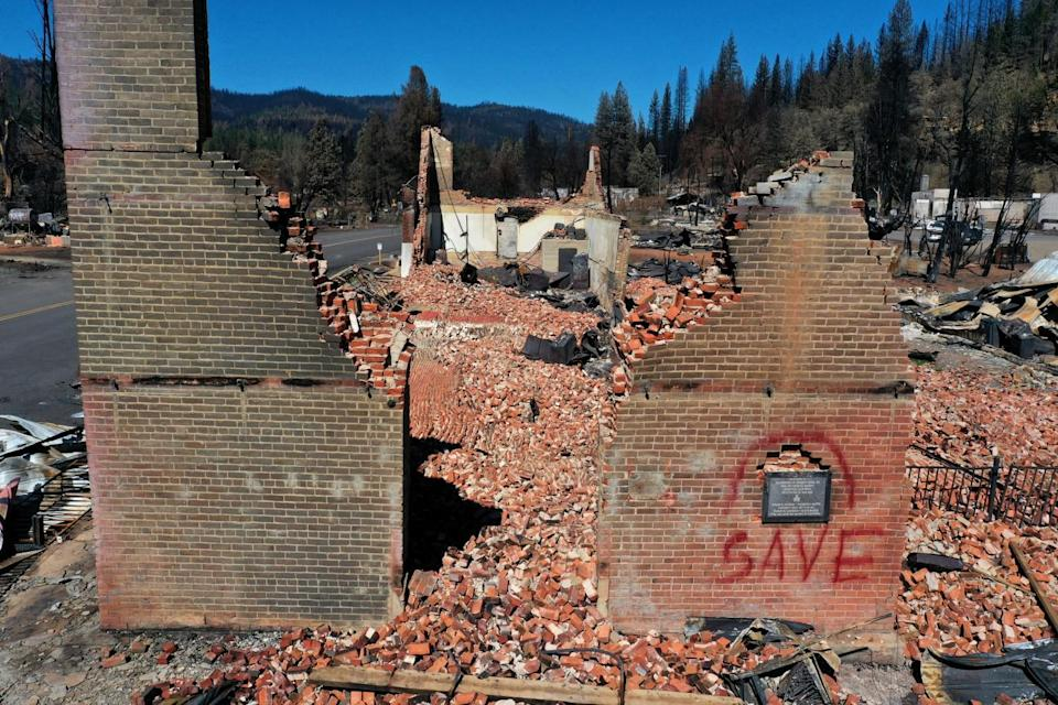 """Two brick walls stand amid rubble, one with the word """"save"""" painted on it"""