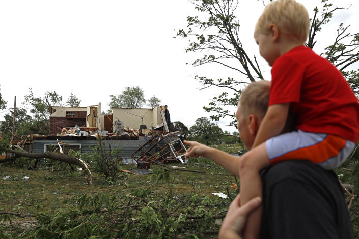Woodridge, Ill., resident Jesse Wallace points out one of the severely damaged homes to his three-year-old son Chris Wallace, after a tornado passed through the area on Monday, June 21, 2021. (AP Photo/Shafkat Anowar)