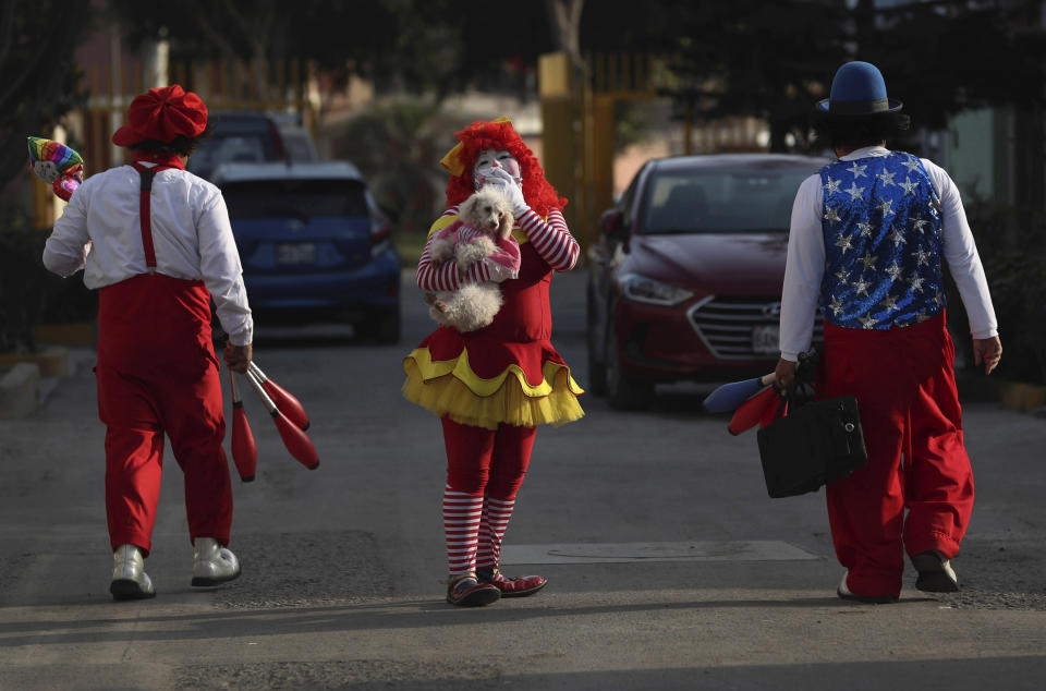 """Circus clown Sara Olazabal, whose performance name is """"Chiquilina,"""" walks between her brothers Alan """"Chiquilin,"""" left, and Michel """"Chiquitin Jr."""" to a home where they will perform a show outside and the children will watch through windows, in a poor neighborhood on the outskirts of Lima, Peru, Monday, July 20, 2020. The Olazabal family also started selling online performances for about $3 per viewer after the COVID-19 lockdown put an end to their circus performances. (AP Photo/Martin Mejia)"""