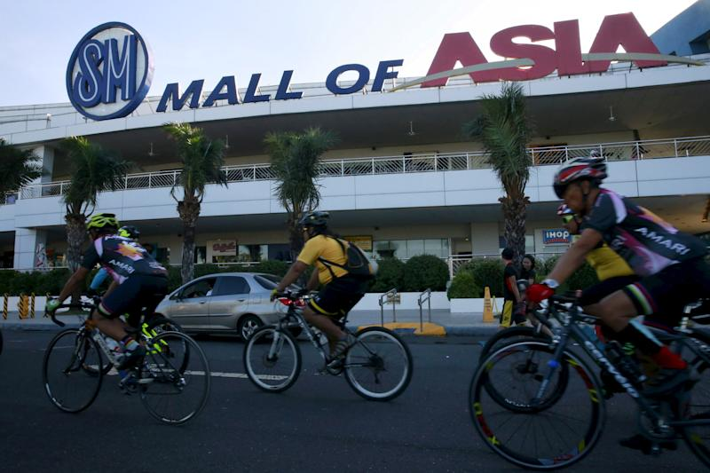 FILE PHOTO: Cyclists ride along a main street of SM Mall of Asia in Pasay City, Metro Manila on February 13, 2016. REUTERS/Romeo Ranoco/Files
