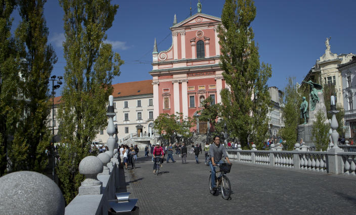 "Cyclists cross a bridge in downtown Ljubljana, Slovenia, Tuesday, Sept. 25, 2012. Once the envy of the former European communist states because of its booming economy and Western-style living standards, Slovenia is becoming a showcase of failed transition, government mismanagement and bad loans. Andrej Plut has always thought he was fortunate to live in Slovenia, at one time the most prosperous of the former republics of Yugoslavia and a star among the eastern European states that joined the EU after the fall of communism. The 55-year-old dentist can't figure out what went wrong with his tiny Alpine state, which now faces one of the worst recessions and financial system collapses among the crisis-stricken 17-country group that uses the euro. ""We used to live so well,"" Plut said. ""Now, we don't know what tomorrow brings."" (AP Photo/Darko Bandic)"
