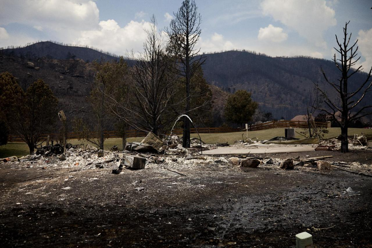 """The remains of a burned structure are left in the Mountain Shadow neighborhood devastated by raging wildfires, Friday, June 29, 2012, in, Colorado Springs, Colo. After declaring a """"major disaster"""" in the state early Friday and promising federal aid, President Obama got a firsthand view of the wildfires and their toll on residential communities. More than 30,000 people have been evacuated in what is now the most destructive wildfire in state history. (AP Photo/Carolyn Kaster)"""