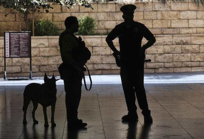 Los Angeles Metro Police and K-9 stand at the entrance to Union Station in Los Angeles on Tuesday, Aug. 14, 2018 prior to a news conference by The Transportation Security Administration (TSA) administrator David P. Pekoske. Pekoske talked about the ThruVision suicide vest-detection technology that reveals a suspicious objects on people. Aiming to stay ahead of an evolving threat against transit systems worldwide, officials in Los Angeles are testing out the airport-style body scanners that screen subway passengers for weapons and explosives. (AP Photo/Richard Vogel)