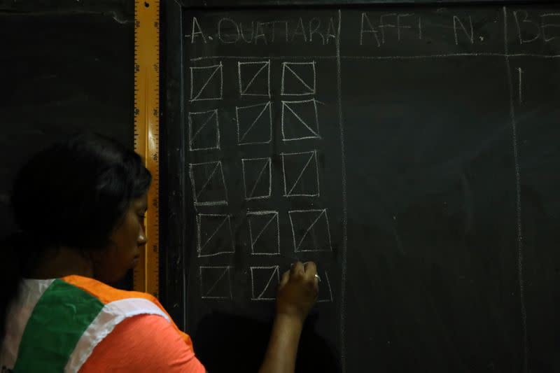 Official tallies the ballots on a chalkboard during the presidential election in Abidjan