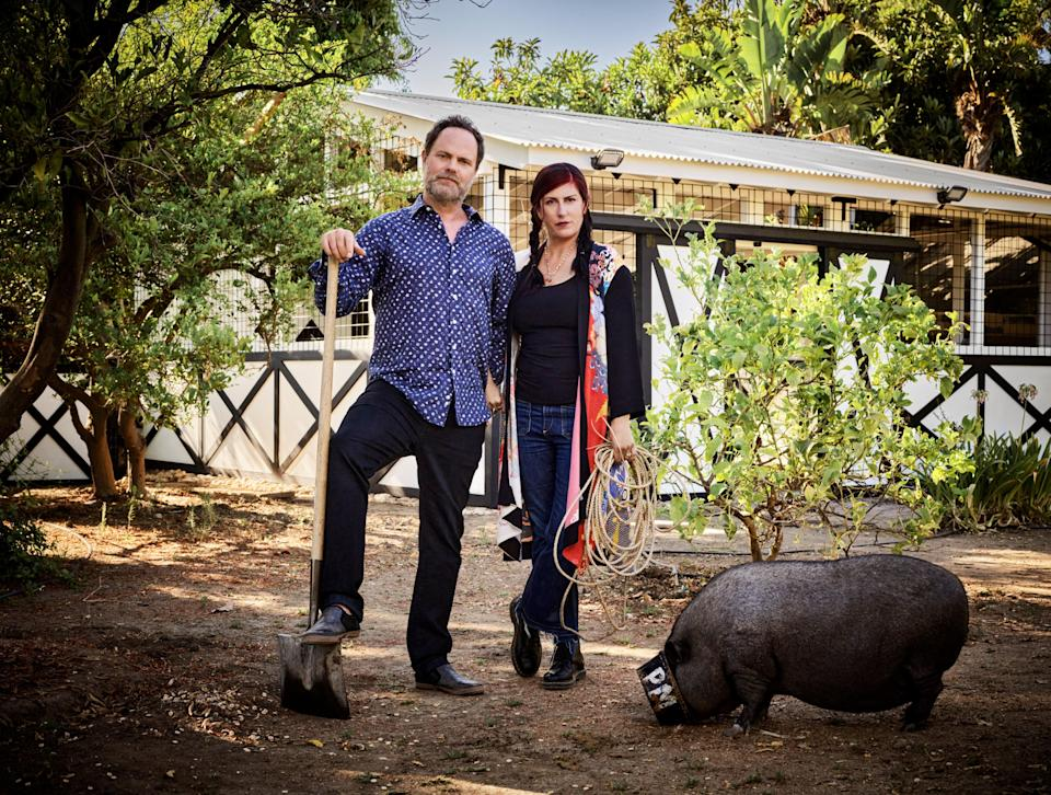 Wilson and Reinhorn strike an American Gothic pose by the barn. Amy, one of the couple's two pigs, remains ever vigilant for snacks.