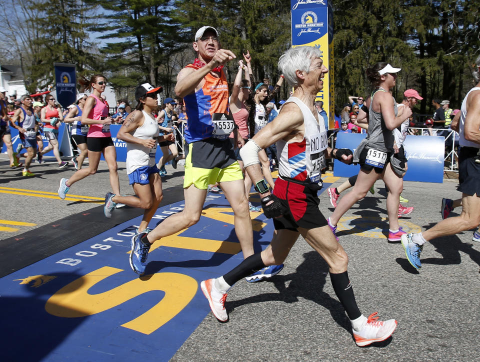 FILE - In this April 17, 2017, file photo, Leeland Cole-Chu (15537) identifies Ben Beach, center, as he crosses the start line running his 50th consecutive Boston Marathon in Hopkinton, Mass. Ben Beach has experienced a little bit of everything while running in a record 53 consecutive Boston Marathons — from New England's unpredictable weather to a diagnosis with dystonia to the 2013 bombing to last year's pandemic disruption.(AP Photo/Mary Schwalm, File)