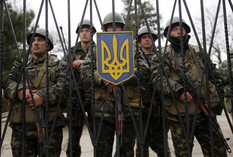 Ukrainian soldiers guard a gate of an infantry base in Privolnoye, Ukraine, Sunday, March 2, 2014. Hundreds of unidentified gunmen arrived outside Ukraine's infantry base in Privolnoye in its Crimea region. The convoy includes at least 13 troop vehicles each containing 30 soldiers and four armored vehicles with mounted machine guns. The vehicles — which have Russian license plates — have surrounded the base and are blocking Ukrainian soldiers from entering or leaving it. (AP Photo/Darko Vojinovic)