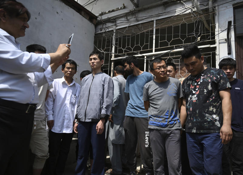FILE - In this May 9, 2019, file photo, a Pakistani official takes pictures of detained Chinese nationals on alleged involvement in a trafficking gang to lure Pakistani women into fake marriages, arrive at a court in Islamabad, Pakistan. Christian girls are being lured into marriages with Chinese men, whom they are told are Christian and wealthy only to end up trapped in China, married to men who are neither Christian nor well-to-do, and some are unable to return home. (AP Photo/B.K. Bangash)