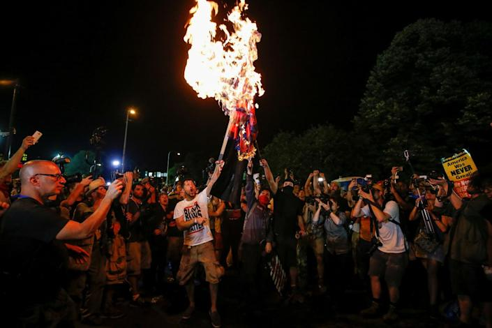 <p>Protesters from various organizations surround men who were burning a modified American flag along the perimeter walls of the 2016 Democratic National Convention in Philadelphia, Pa., on July 27, 2016. (Photo: Adrees Latif/Reuters)</p>