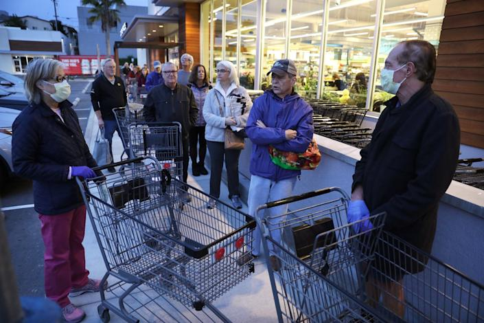 "Shoppers including Eileen Oda Leaf, 67, left, and her husband Dave Leaf, 67, right, both wearing protective masks, line up outside Gelson's Market in Manhattan Beach. <span class=""copyright"">(Christina House/Los Angeles Times)</span>"