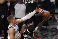 Los Angeles Clippers guard Paul George, right, shoots as Dallas Mavericks center Kristaps Porzingis defends during the first half in Game 5 of an NBA basketball first-round playoff series Wednesday, June 2, 2021, in Los Angeles. (AP Photo/Mark J. Terrill)