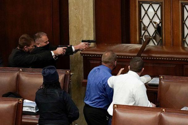 PHOTO: U.S. Capitol Police with guns drawn watch as rioters try to break into the House Chamber at the U.S. Capitol on Jan. 6, 2021, in Washington, D.C.  (J. Scott Applewhite/AP)