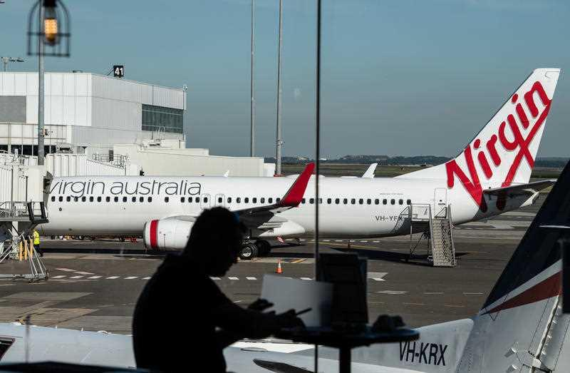 A man sits at a cafe in front of a Virgin Australia plane at Sydney Airport.