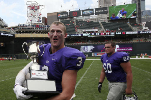 FILE - In this Sept. 23, 2017, file photo, St. Thomas wide receiver Tanner Vik walks on the field with the Holy Grail trophy after the team's win over St. John's in an NCAA college football game, in Minneapolis. St. John's and St. Thomas will stage their final game as Minnesota Intercollegiate Athletic Conference foes at U.S. Bank Stadium this fall. The 90th edition in the series will be played Nov. 7, 2020. (Anthony Souffle/Star Tribune via AP, File)