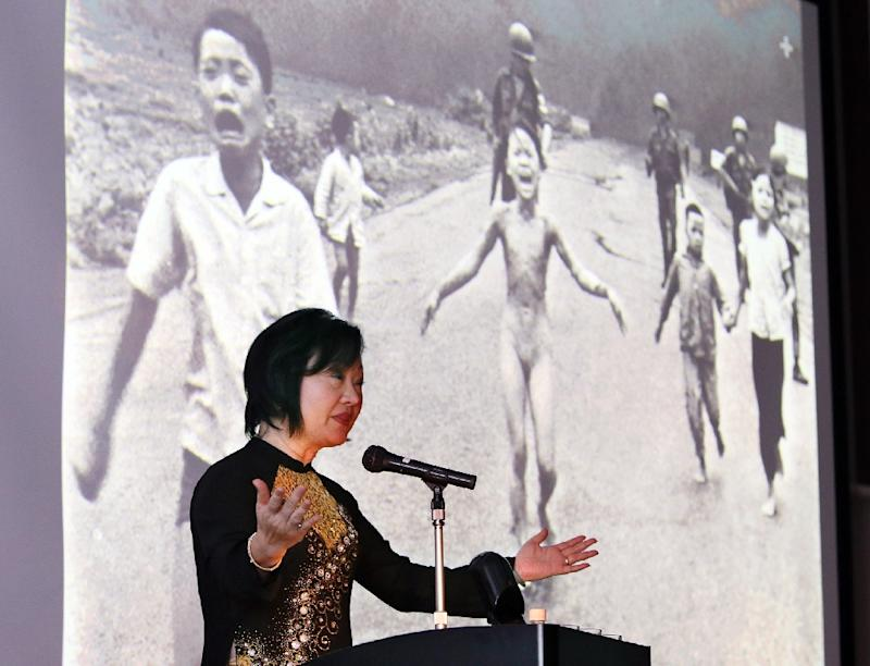 Phan Thi Kim Phuc delivers a speech in front of a Pulitzer-Prize-winning photo depicting her running naked on June 8, 1972 during the Vietnam war, during a lecture meeting in Nagoya, Japan on April 13, 2013