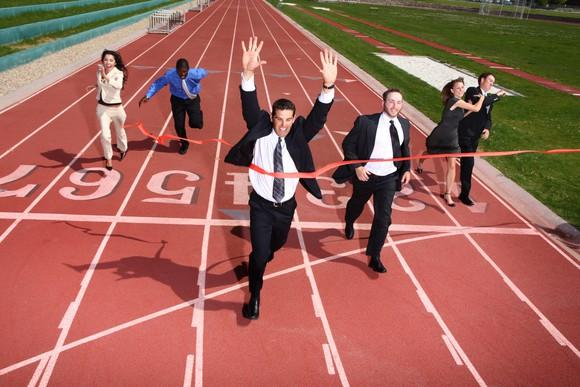 Business people running to a finish line on a running track.