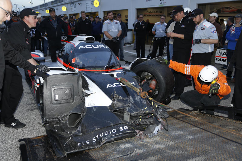 FILE - In this Thursday, Jan. 23, 2020, file photo, safety personnel unload the wreckage of the Acura Team Penske car driven by Ricky Taylor, not pictured, during qualifying for the Rolex 24 hour auto race at the Daytona International Speedway, in Daytona Beach Fla. The Penske crew had it repaired in time to get back on track and ready for the Saturday start of the endurance race. (AP Photo/Reinhold Matay)