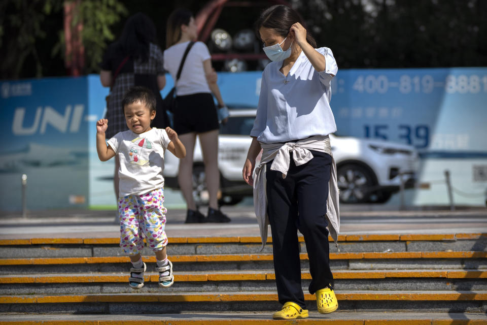 A woman watches as a child jumps down steps at a public park in Beijing, Saturday, Aug. 21, 2021. China will now allow couples to have a third child as the country seeks to hold off a demographic crisis that threatens its hopes of increased prosperity and global influence. (AP Photo/Mark Schiefelbein)