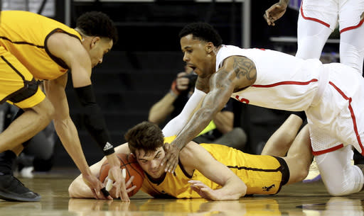 Wyoming's Hunter Thompson, center, Justin James, left, and New Mexico's Corey Henson reach for a loose ball during the first half of an NCAA college basketball game in the Mountain West Conference tournament Wednesday, March 13, 2019, in Las Vegas. (AP Photo/Isaac Brekken)