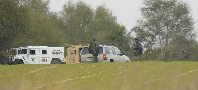 Armed law enforcement personnel station themselves near the property of Jimmy Lee Sykes, Monday, Feb. 4, 2013 in Midland City, Ala. Officials say they stormed a bunker in Alabama to rescue a 5-year-old child being held hostage there after Sykes, his abductor, was seen with a gun. (AP Photo/AL.com, Joe Songer)