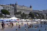 Members of the public take a swim in the sea in front of the Carlton hotel ahead of the 74th international film festival, Cannes, southern France, July 5, 2021. The Cannes film festival runs from July 6 - July 17, 2021. (AP Photo/ Brynn Anderson)