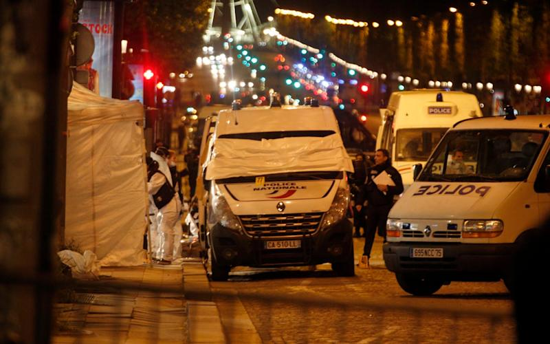 Forensic experts and police officers examine evidence from a police van on the Champs Elysees - Credit: AP