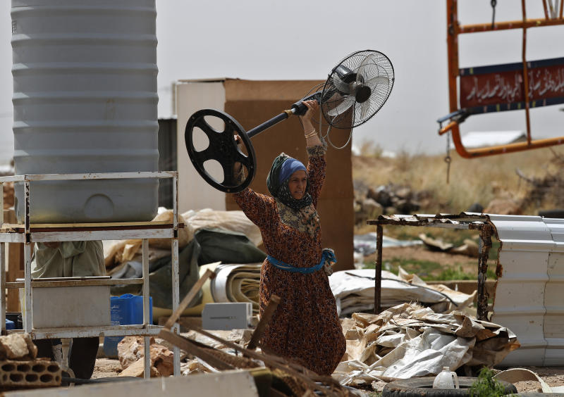A Syrian woman carries a fan, as she removes her belongings to evacuate an informal refugee camp after a fight broke out last week between camp residents and Lebanese firefighters who arrived to put out a fire, in Deir Al-Ahmar, east Lebanon, Sunday, June 9, 2019. Dozens of Syrian refugees have dismantled their tents in a camp they lived in for years in eastern Lebanon after authorities ordered their evacuation following a brawl with locals. Lebanon hosts over 1 million Syrian refugees who fled the war next door since 2011, overwhelming the country of nearly 5 million. (AP Photo/Hussein Malla)