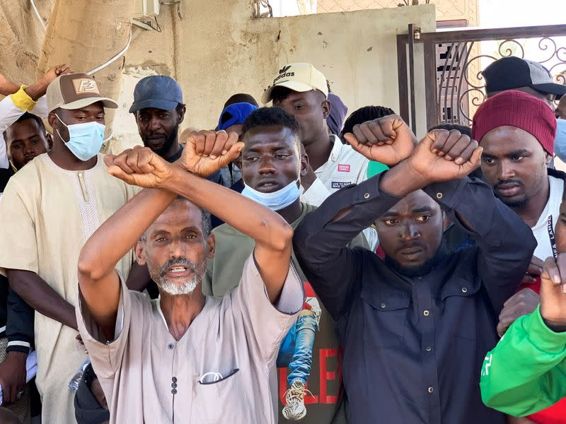 Migrants gesture as they wait outside the United Nations High Commissioner for Refugees (UNHCR) negotiation office in Tripoli