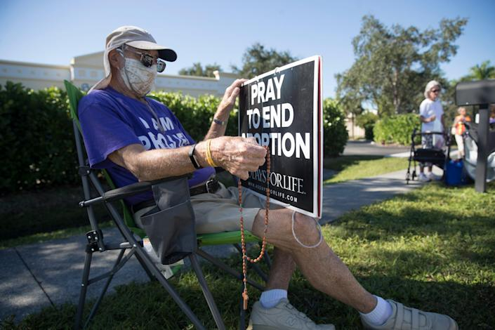 """Fort Myers resident, Brian Walker protests abortion outside of Planned Parenthood in Fort Myers on Thursday, October 15, 2020. He condemned the incident involving the molotov cocktail being thrown at the building over last weekend. He said """"That's not what we are all about, it's wrong, we are all about love."""""""