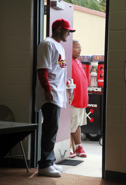 St. Louis Cardinals catcher Yadier Molina stands at a door and waits for his family to arrive for news conference at spring training announcing his signing a new five-year contract with the Cardinals, Thursday, March 1, 2012, in Jupiter, Fla. The new contract keeps Molina with the Cardinals through the 2017 season with a mutual option for 2018. (AP Photo/Jeff Roberson)