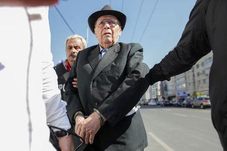Ioan Ficior, 89, a Romanian communist-era labour prison commander is escorted by police at the end of his trial in Bucharest, Romania, March 29, 2017. Inquam Photos/Liviu Florin Albei via REUTERS