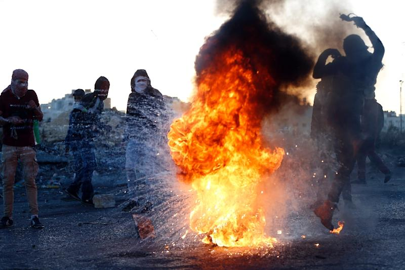 A Palestinian protester kicks a burning tyre during clashes with Israeli forces in the West Bank city of Ramallah on December 16, 2017 (AFP Photo/ABBAS MOMANI)