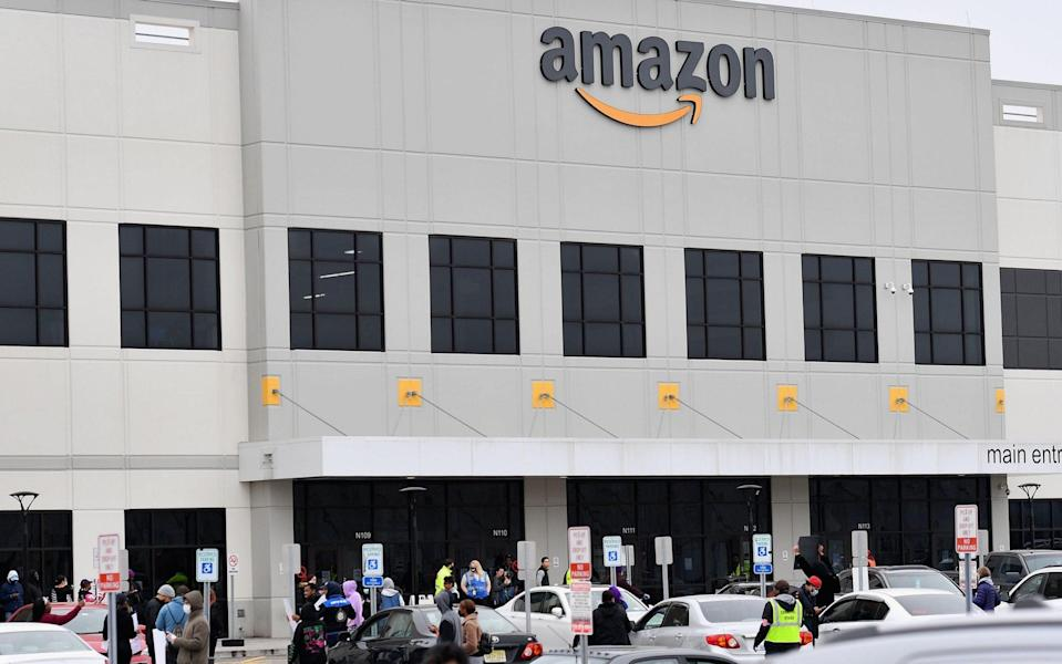 In this file photo taken on March 30, 2020, Amazon workers at Amazon's Staten Island warehouse strike in demand that the facility be shut down and cleaned after one staffer tested positive for the coronavirus in New York - ANGELA WEISS/AFP