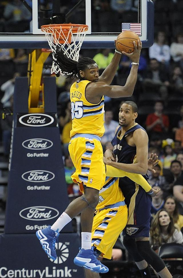 Denver Nuggets forward Kenneth Faried, left, grabs a rebound over New Orleans Pelicans center Alexis Ajinca, of France, right, in the first half of an NBA basketball game on Wednesday, April 2, 2014, in Denver. (AP Photo/Chris Schneider)