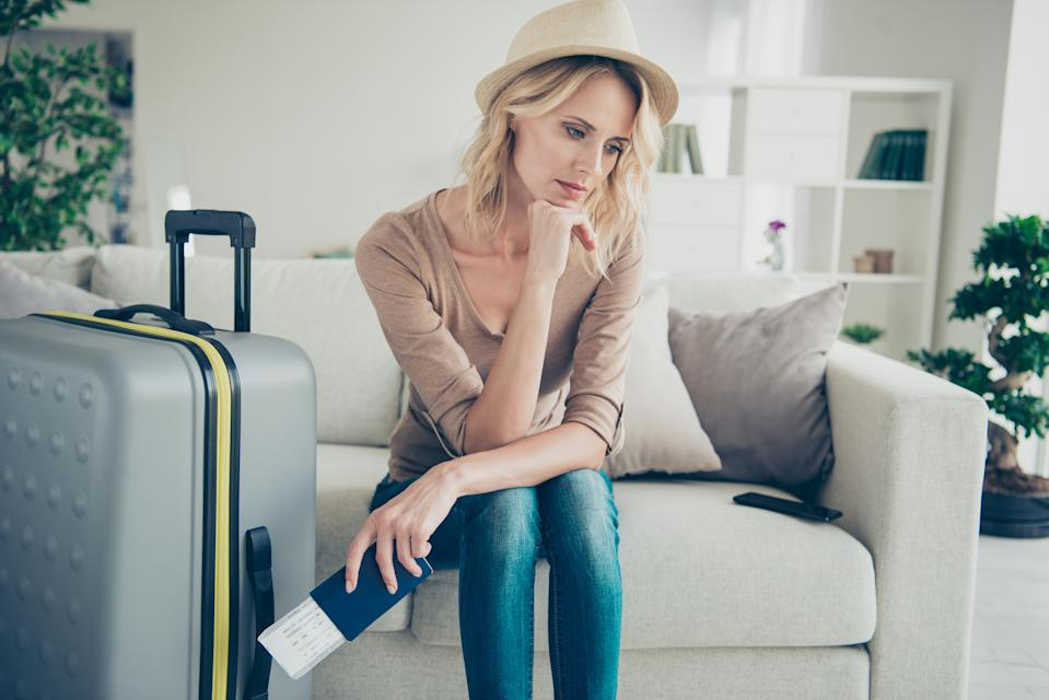 Gorgeous attractive lady in her casual clothes denim jeans blond curly wavy hair she sit on cozy comfort couch sofa inside modern apartment room hold boarding pass in hands look sad