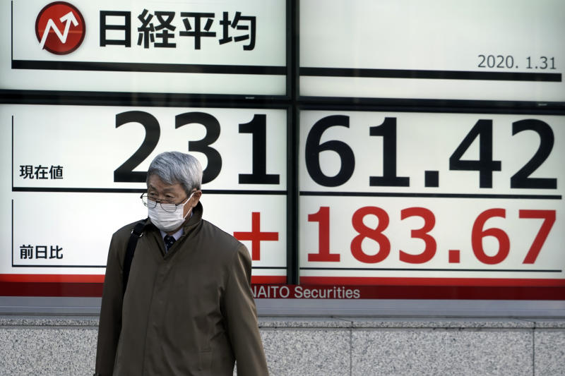 A man walks past an electronic stock board showing Japan's Nikkei 225 index at a securities firm in Tokyo Friday, Jan. 31, 2020. Shares are mixed in Asia after the World Health Organization declared the outbreak of a new virus that has spread from China to more than a dozen countries a global emergency. (AP Photo/Eugene Hoshiko)