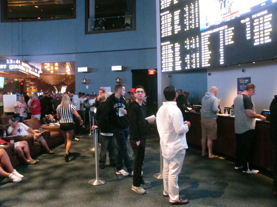 In this Sept. 9, 2018 photo, gamblers line up to make sports bets at the Ocean Casino Resort in Atlantic City, N.J. Figures released on Thursday, Oct. 15, 2020 show New Jersey broke its own recently set U.S. record for the most money bet on sports in a single month in September, when more than $748 million was bet on sports. (AP Photo/Wayne Parry)