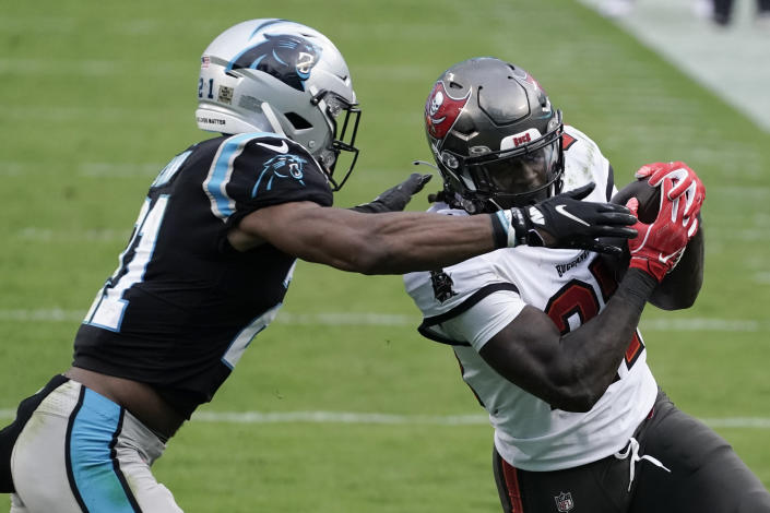 Tampa Bay Buccaneers running back Ronald Jones (27) runs agaqinst Carolina Panthers outside linebacker Jeremy Chinn (21) during the second half of an NFL football game, Sunday, Nov. 15, 2020, in Charlotte , N.C. (AP Photo/Gerry Broome)