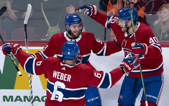 Montreal Canadiens' Victor Mete celebrates his goal against the Minnesota Wild with teammates Shea Weber, left, and Joel Armia, right, during first-period NHL hockey game action in Montreal, Thursday, Oct. 17, 2019. (Paul Chiasson/The Canadian Press via AP)